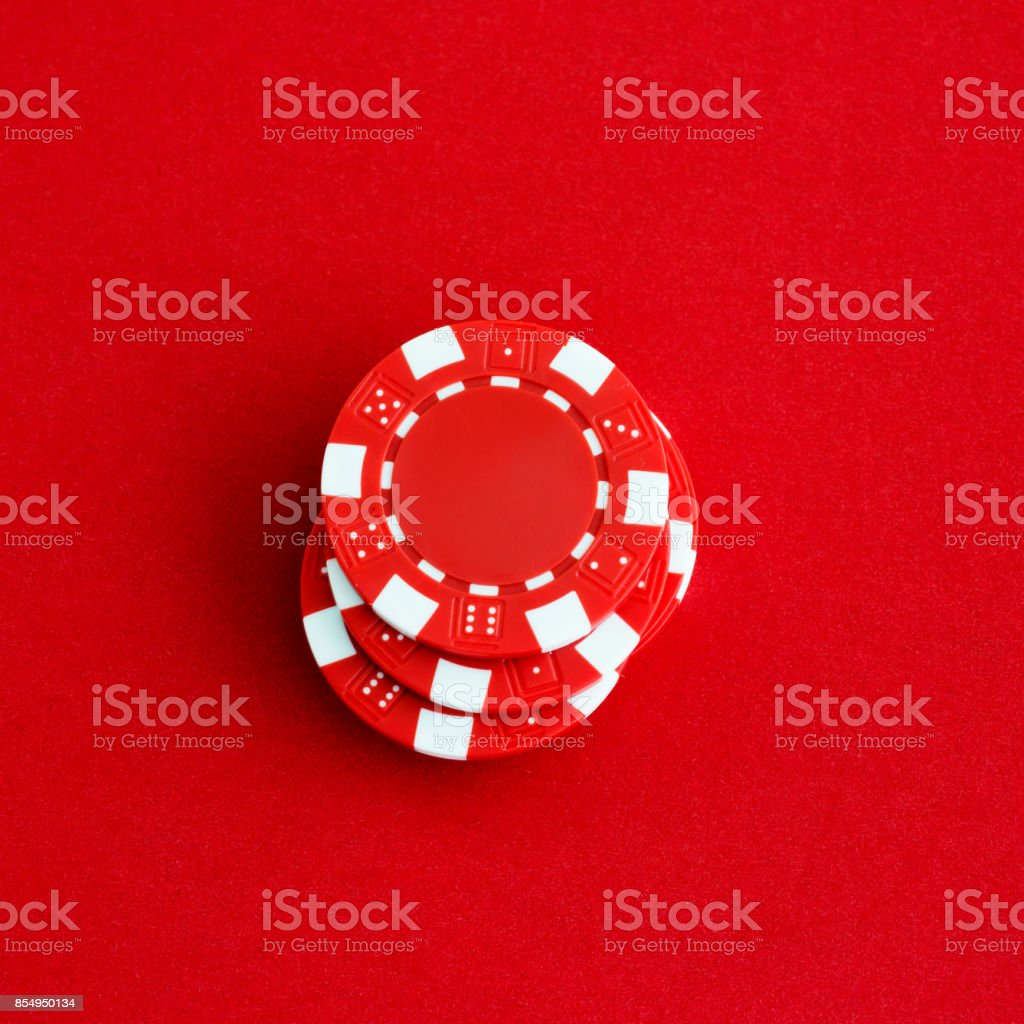 A stack of poker chips on red background stock photo
