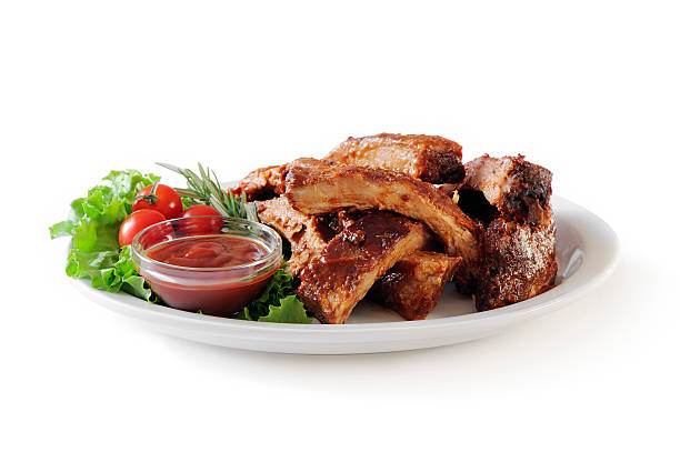 """Stack of pork ribs """"Plate of cut baby back ribs with barbecue sauce,lettuce and cherry tomatoes isolated on white. More ribs..."""" pork stock pictures, royalty-free photos & images"""