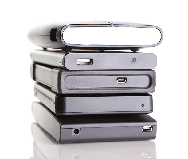 stack of portable hard drives on white - external hard disk drive stock photos and pictures