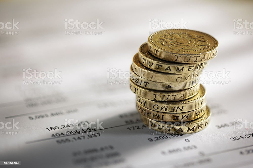 Stack of pound coins on financial figures stock photo
