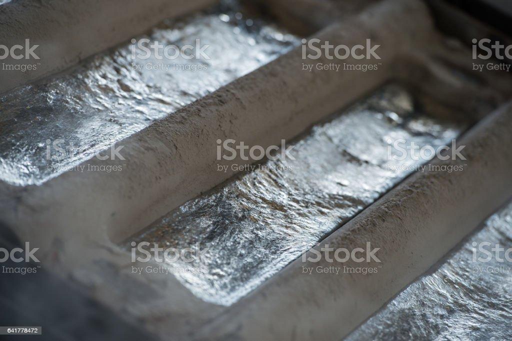 Stack of raw aluminum ingots in aluminum profiles factory - Photo