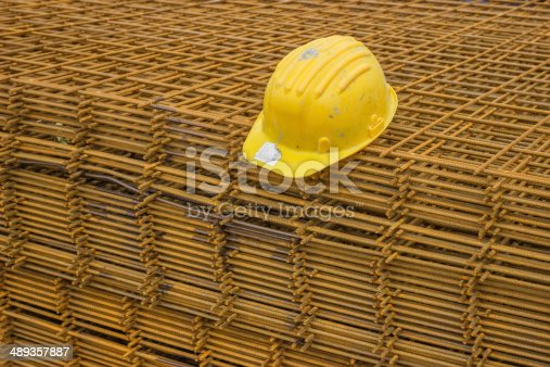 Stack of rebar grids with yellow helmet at the construction site. Selective focus.