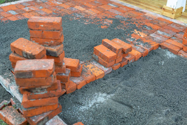 Stack of reclaimed bricks from a fallen chimney being used with sand for a new patio. stock photo