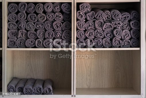 Stack of rolled gray towels on the wooden shelf in the beauty salon.