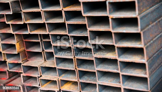 istock Stack of rusty square steel tubes 908683544