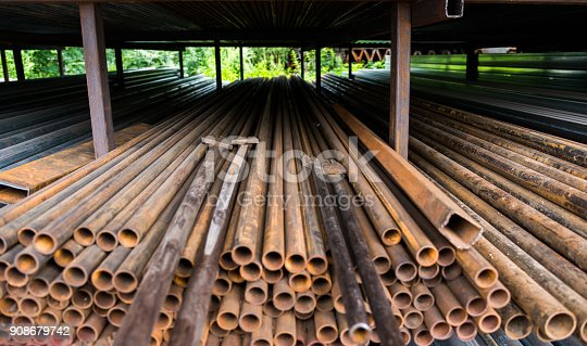 istock Stack of rusty steel pipes 908679742