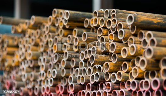 istock Stack of rusty steel pipes 908682374