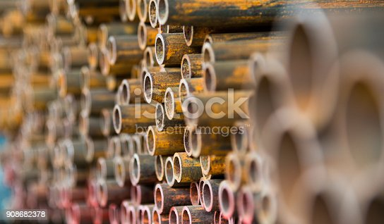 istock Stack of rusty steel pipes 908682378