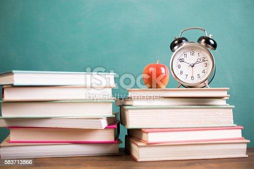 istock Stack of school textbooks, alarm clock, apple and chalkboard. 583713866