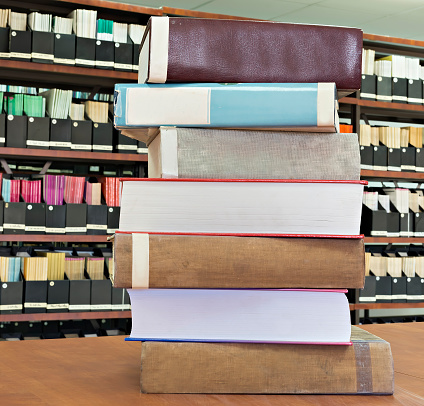 Stack of scientific books in old scientific library, knowledge and science concept