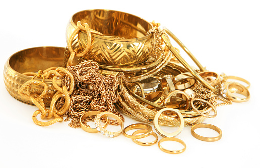 Scrap gold chains, rings, and other jewellery on white background