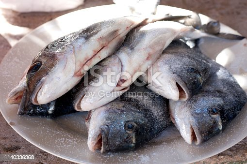 istock Stack of sea bream, Dorado fish on plate 1140336368