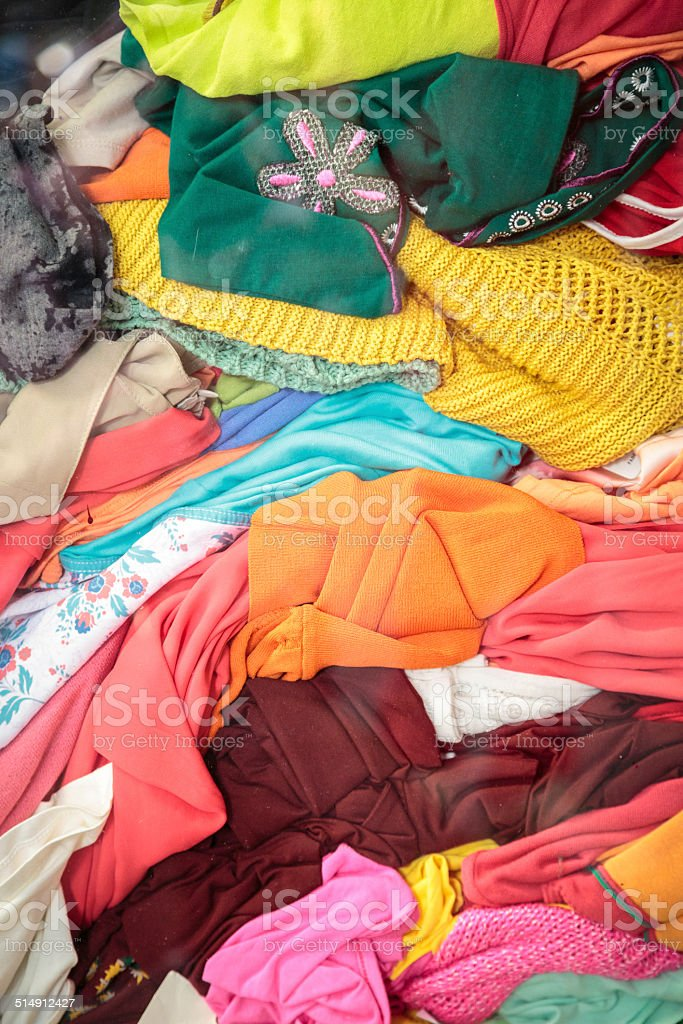 stack of second hand clothes in a shop window stock photo