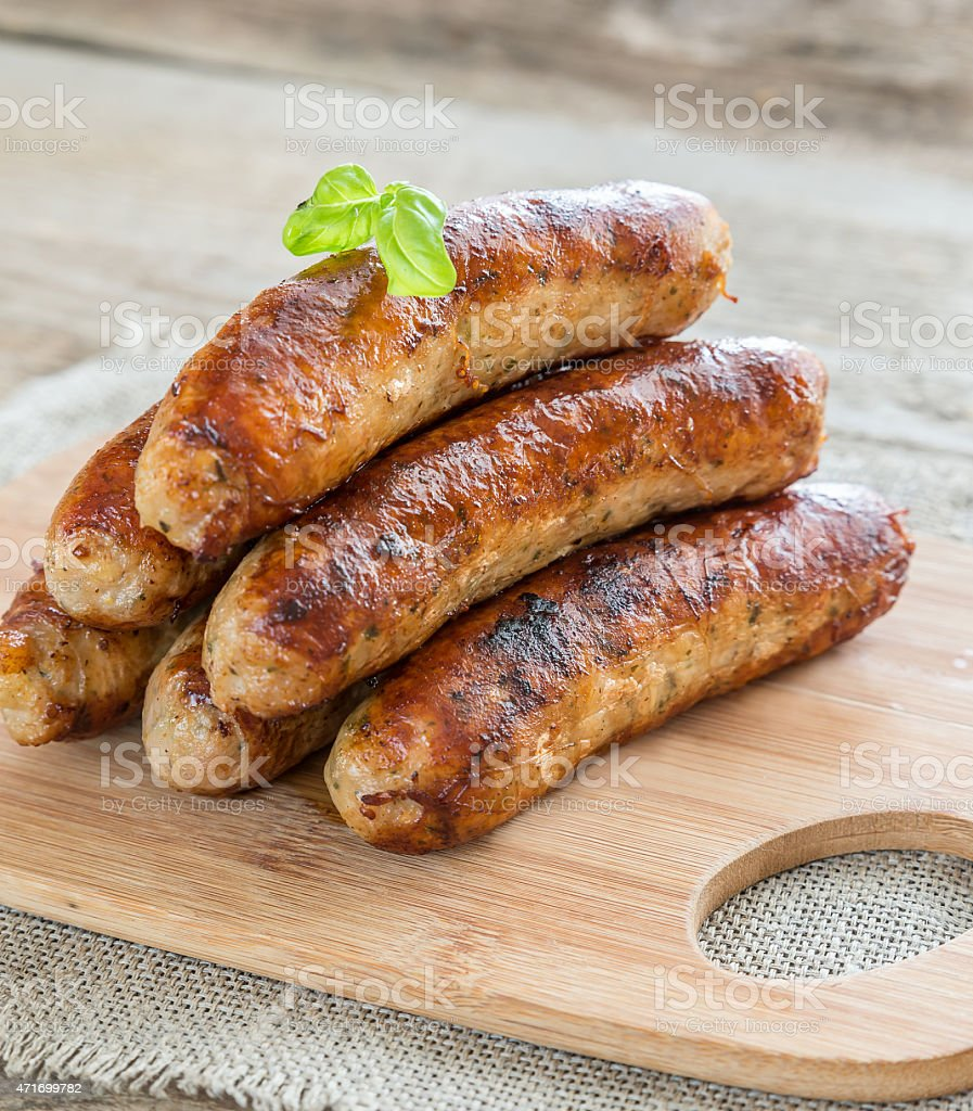 A stack of seven grilled sausages on a wood cutting board stock photo