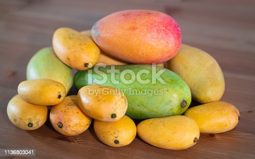 Stack of several varieties of Mangoes of different size and colors
