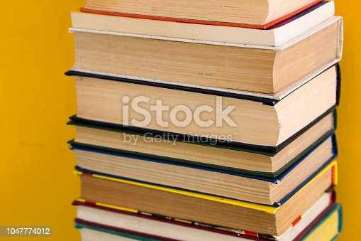 480762174istockphoto Stack of shabby books in library on yellow background 1047774012
