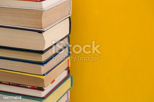 480762174istockphoto Stack of shabby books in library on yellow background 1047774016