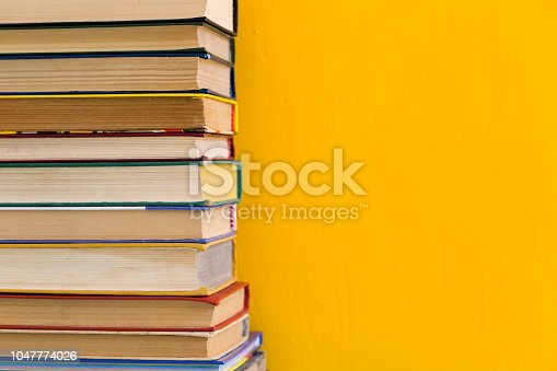 480762174istockphoto Stack of shabby books in library on yellow background 1047774026