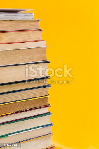 480762174istockphoto Stack of shabby books in library on yellow background 1047774040