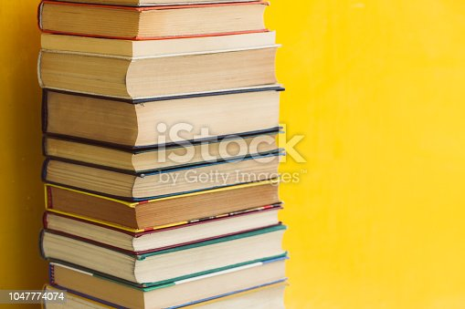 480762174istockphoto Stack of shabby books in library on yellow background 1047774074