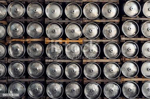 Stack of shiny stainless steel beer kegs outside in factory