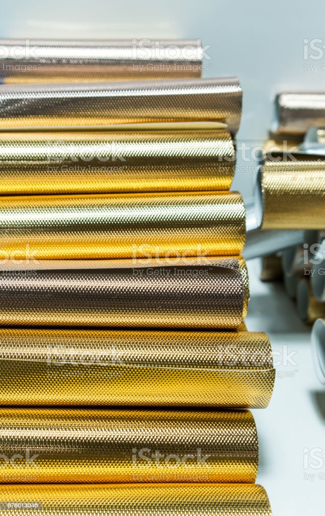 Stack of shiny golden gift-wrapping paper rolls for texture and pattern background. stock photo