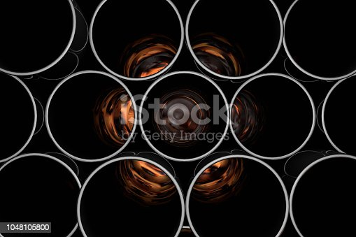 istock Stack of shiny metal steel pipes with flame 1048105800