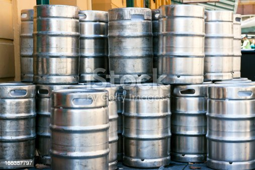 Stack of shiny stainless steel beer kegs outside of pub, full frame horizontal composition