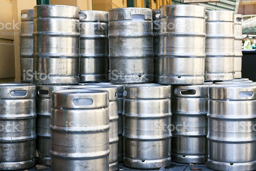 Stack of shiny stainless steel beer kegs outside of pub stock photo