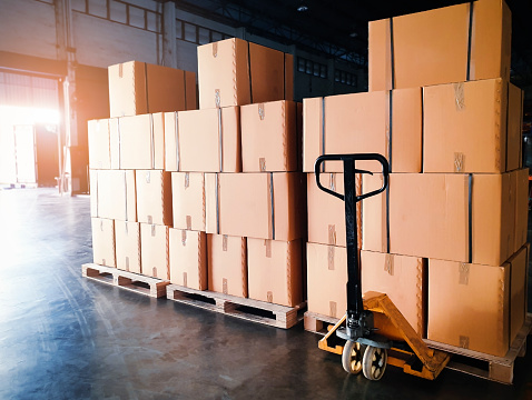 Stack of shipments boxes on wooden pallets at interior warehouse storage. Cargo export. Warehouse industry logisics and transport.