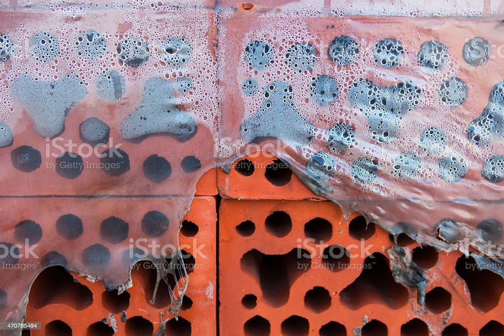 Stack of silicate bricks in misted torn polyethylene. Closeup stock photo