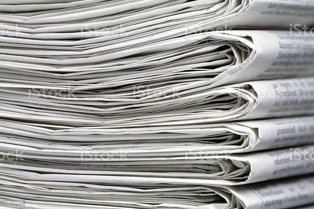 A stack of six or seven newspapers stock photo