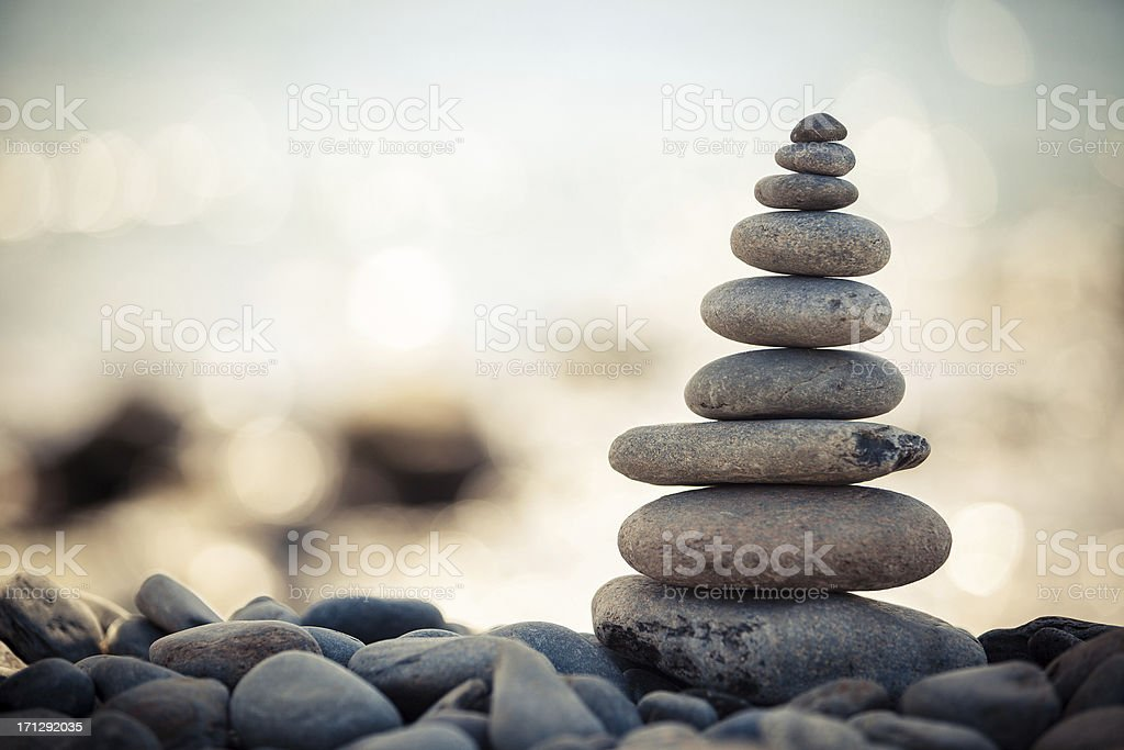 Stack of smooth stones over other stones on a beach royalty-free stock photo