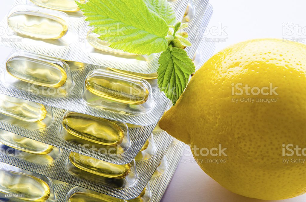 Stack of soft capsules and lemon royalty-free stock photo
