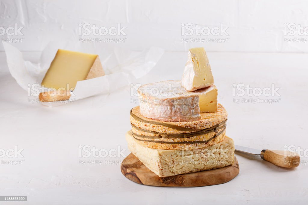 Stack Of Soft French Cows Milk Cheese On A Cutting Board On White Camembert Livarote Pontleveque Cheese From Normandy Copy Space Stock Photo Download Image Now Istock