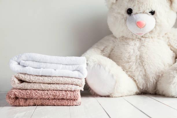 stapel von spa handtücher auf weißer holztisch mit weißen kuscheltier bär auf hintergrund. kinder waschen konzept - hausmittel gegen falten stock-fotos und bilder