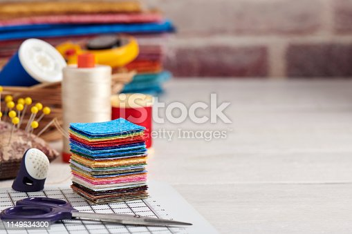 Stack of square pieces of colorful fabrics, accessories for quilting
