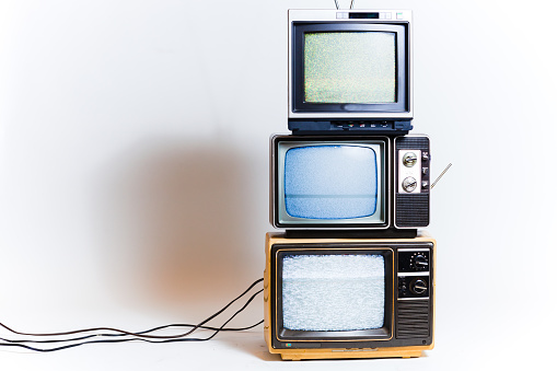 Stack of three retro tvs with static on the screens. Shot on a white background.