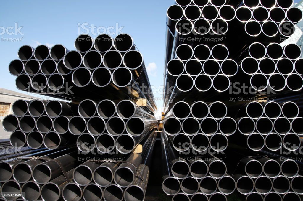 stack of steel tubes against blue sky stock photo
