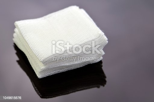 istock Stack of sterile gauze pad on dark background. 1049615576