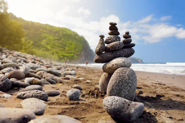 Stack of stones balanced on rocky beach of Pololu Valley, Big Island, Hawaii stock photo