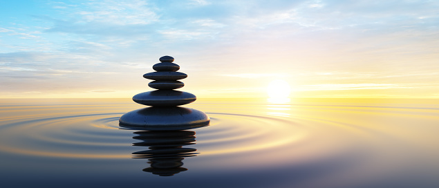 Stack of Stones in calm water with evening clouds