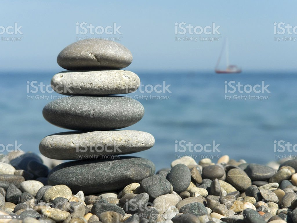 Stack of stones on top of pebbles with sea and yacht behind stock photo