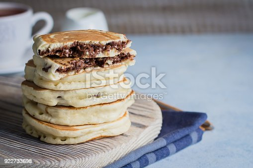 istock Stack of Stuffed chocolate nutella pancakes on vintage wooden board on blue table background with cup of tea. American Breakfast Concept. Copy space 922733698
