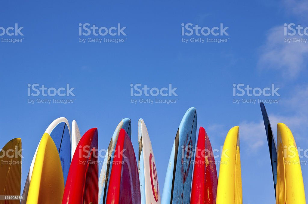 Stack of surfboards by seaside Set of different color surf boards in a stack by ocean Beach Stock Photo