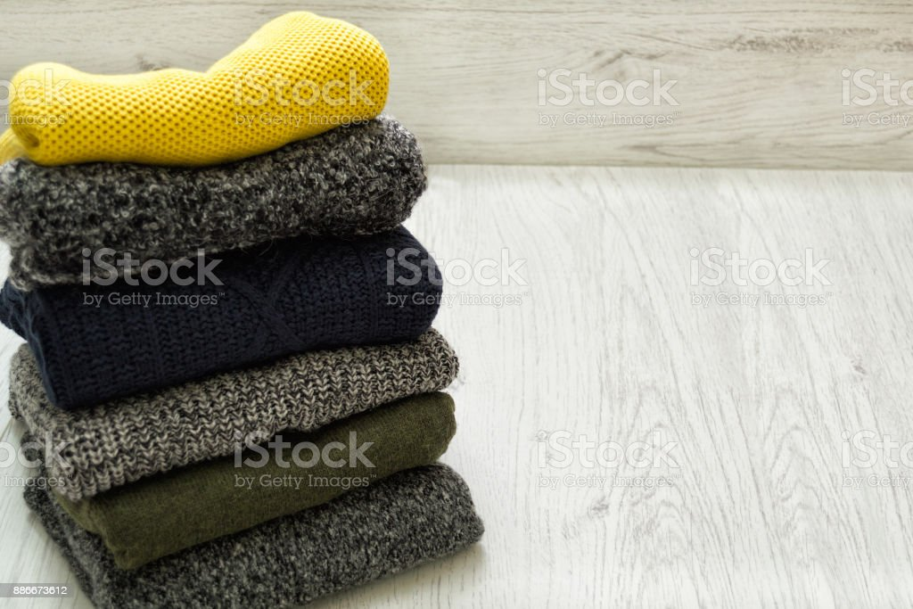 Stack of sweaters on a wooden background. Fashionable concept. stock photo