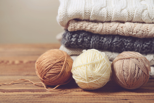 stack of sweaters on a wooden table