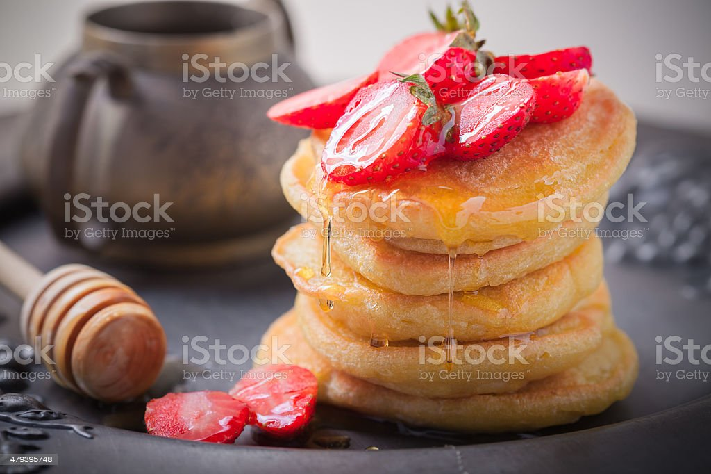 Stack of sweet pancakes with strawberry and honey. stock photo