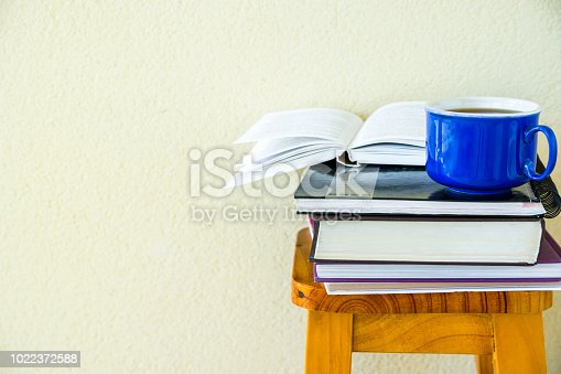 istock Stack of textbooks notepads workbooks blue cup of hot tea on high wooden stool on white wall background. University college education homeschooling learning concept. Authentic lifestyle image 1022372588