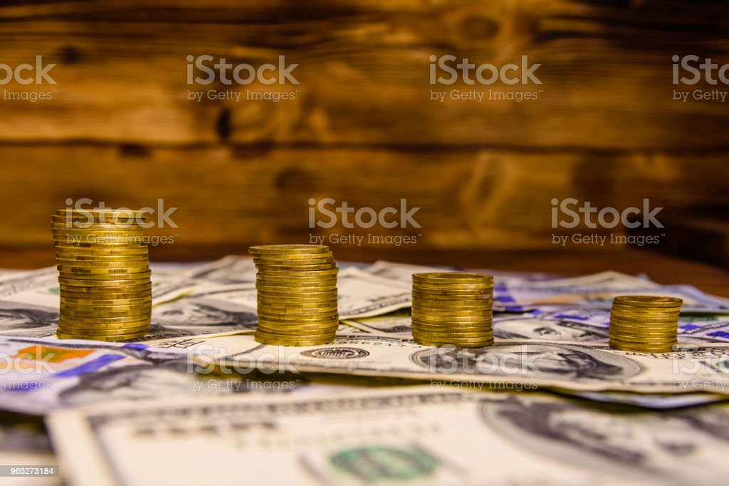 Stack of the coins on the one hundred dollar bills zbiór zdjęć royalty-free